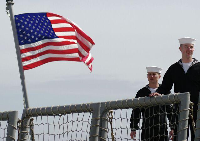 Militares da Marinha dos Estados Unidos junto à bandeira do país