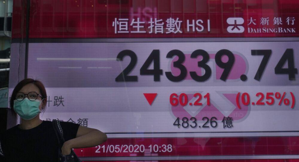 Mulher com máscara para se proteger do coronavírus passa diante de tela com dados da bolsa de valores de Hong Kong, na China