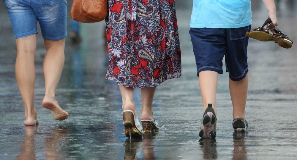 Pedestres andam pela rua durante forte chuva em Moscou.