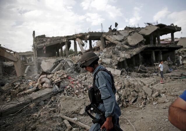 Policial afegão caminha pelo local de uma explosão em Cabul, 7 de agosto de 2015