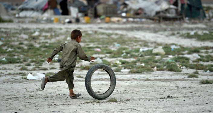 Um menino afegão de nômade Kochi brinca com o pneu perto da sua tenda nos arredores de Kabul. 2 de agosto de 2015