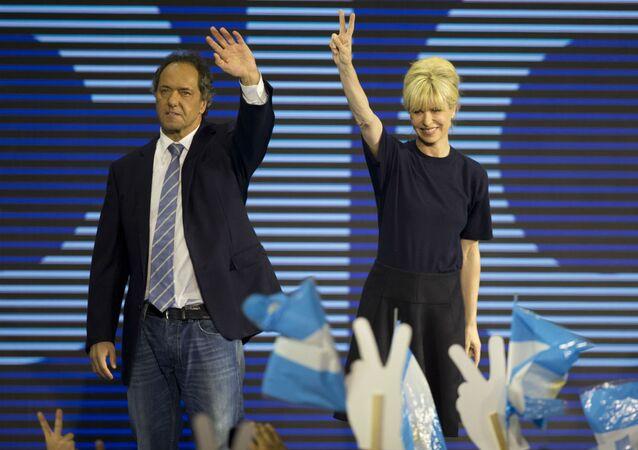 Daniel Scioli e a esposa Karina Rabolini comemoram a vitória nas primárias da Argentina.