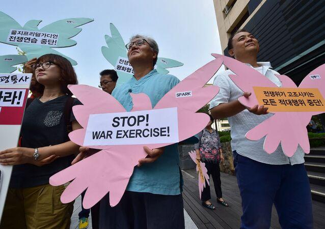 Sul-coreanos se reúnem em frente à Embaixada dos EUA em Seul para pedir uma solução pacífica para os problemas com a Coreia do Norte.