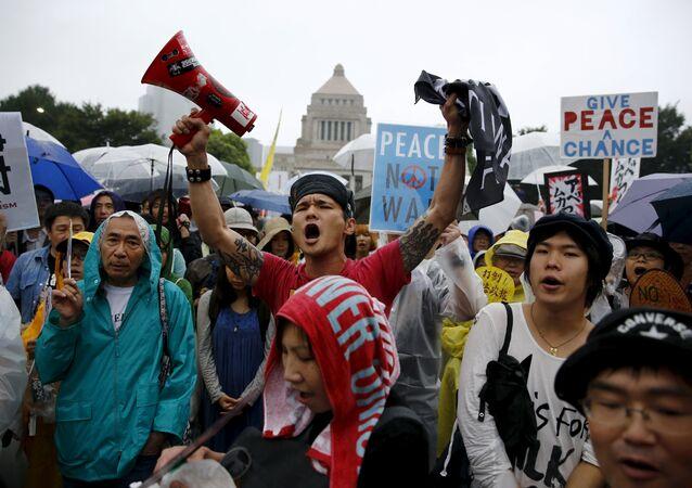 Manifestantes empunham cartazes com slogans contra o primeiro ministro do país, Shinzo Abe e sua política de segurança, do lado de fora do Parlamento japonês em Tóquio