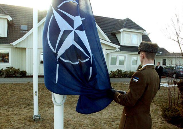Soldado estoniano içando a bandeira da OTAN na cidade de Tallinn