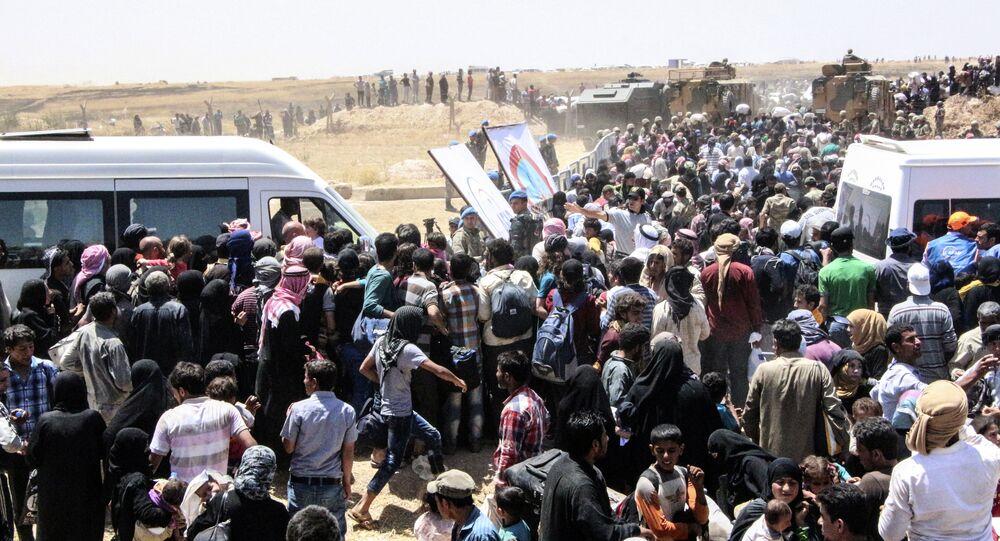 Refugiados sírios estão à espera de transporte após atravessar a fronteira com a Turquia da cidade síria Tal Abyad, em 10 de junho de 2015
