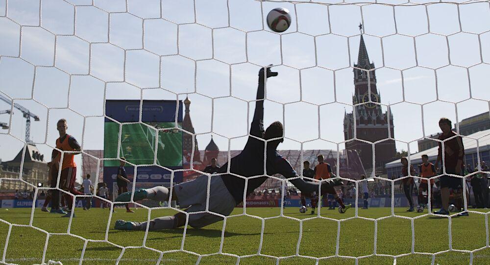 Um goleiro tenta pegar a bola na praça Vermelha (centro de Moscou)
