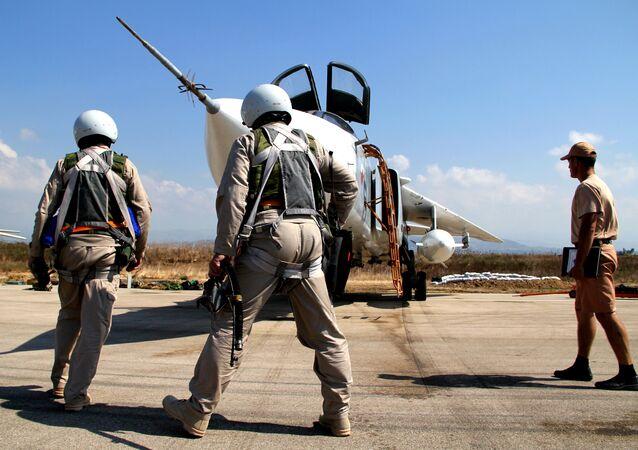Pilotos russos ao lado de um caça Su-24 na Síria