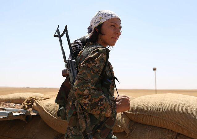 Uma mulher combatente curda da Unidade de Proteção do Povo (YPG) na linha de frente na Síria.