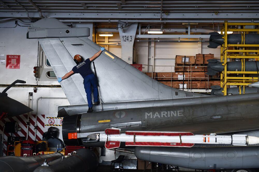 Um técnico francês faz a manutenção de um caça Rafale a bordo do porta-aviões Charles de Gaulle