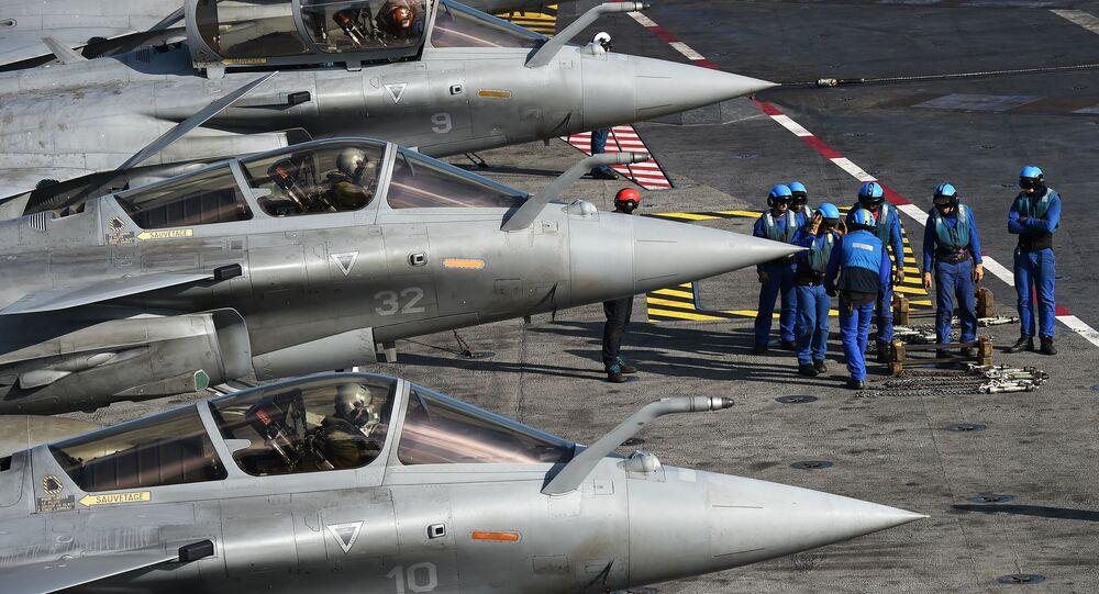 Militares franceses ao lado dos caças Rafale no convés do porta-aviões Charles de Gaulle no Mar Mediterrâneo