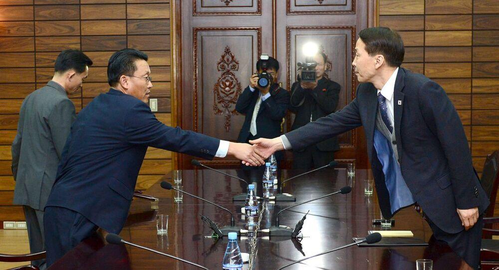 O chefe da delegação sul-coreana, Kim Ki-Woong (dir.) aperta a mão com do seu homólogo norte-coreano, Hwang Chol.