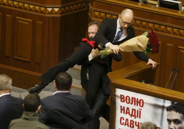 Oleg Barna, deputado da Rada, remove o primeiro-ministro Arseniy Yatsenyuk da tribuna, depois de lhe apresentar um buquê de rosas, durante a sessão do parlamento em Kiev, Ucrânia, 11 de dezembro de 2015