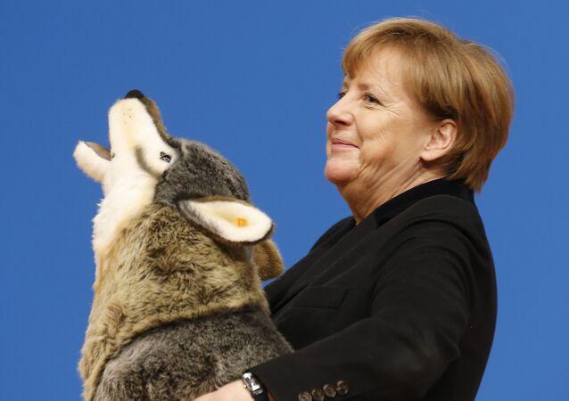 A chanceler alemã Angela Merkel segura um lobo de brinquedo que ganhou de presente durante a convenção do partido dos democratas-cristãos (CDU), em Karlsruhe, Alemanha. 14 de dezembro.