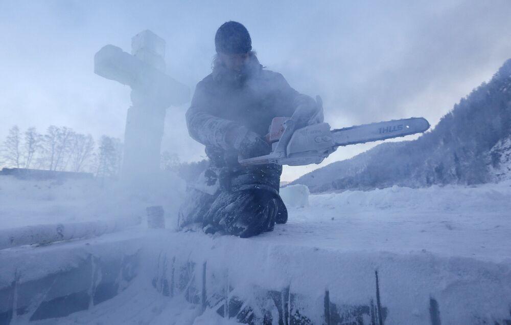 Monge russo prepara local para a realização de mergulhos em água gelada para a celebração da festa de Batismo de Cristo, na região de Krasnoyarsk