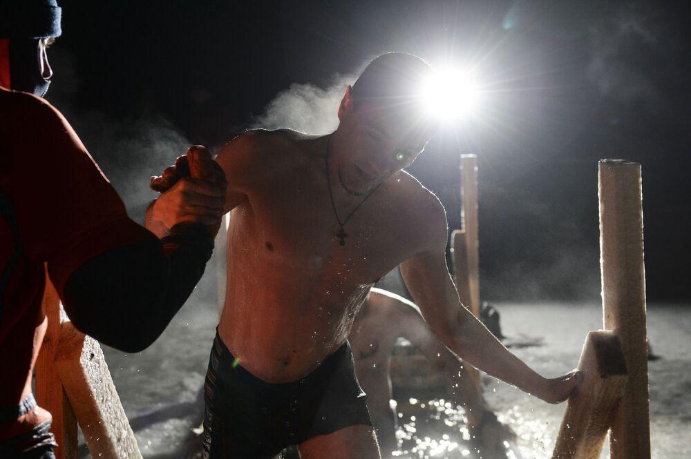 Homem participa de mergulhos noturnos de batismo no lago Shartash, em Ecaterimburgo