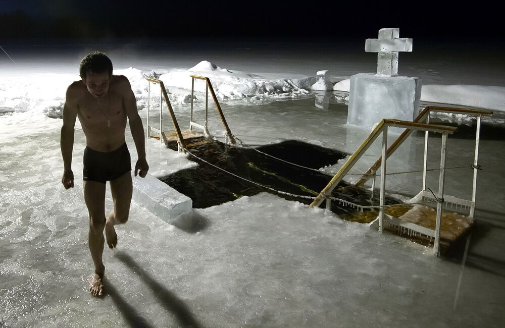 Homem participa de mergulhos noturnos de batismo na região de Valdai