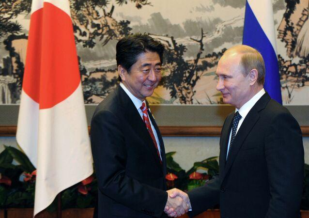 O primeiro-ministro japonês Shindzo Abe e o presidente russo Vladimir Putin apertam as mãos durante o fórum de Cooperação Econômica Ásia-Pacífico em Pequim, China, 4 de novembro de 2014