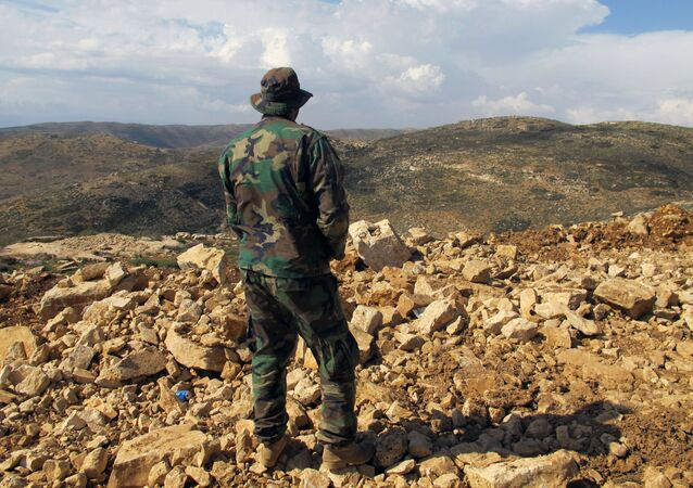 Combatente do Hezbollah em Brital, no Líbano, olha na direção da Síria