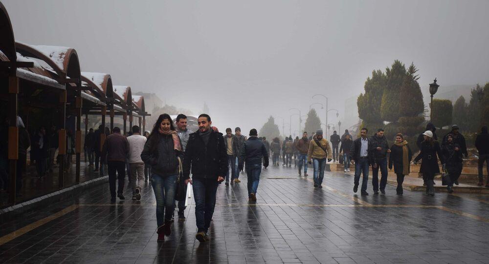 Habitantes de Homs passeiam por uma das ruas principais da cidade, Síria