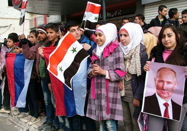 Jovens sírios fazem fila na cidade de Kessab para obter ajuda humanitária russa
