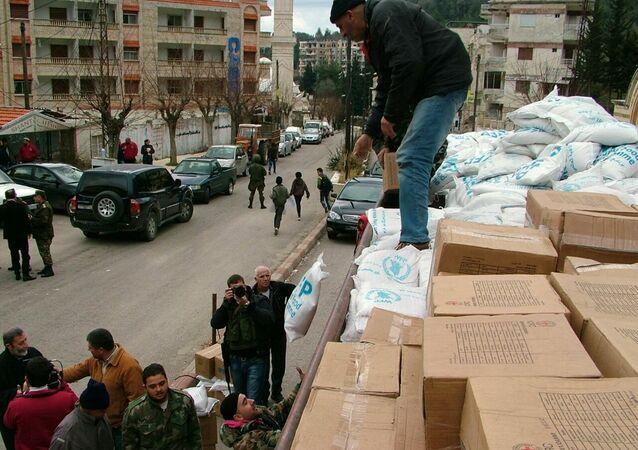 Militares descargam ajuda humanitária do caminhão em uma rua da cidade de Kessab, na província síria de Latakia