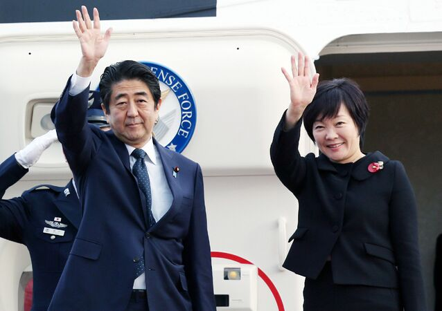 Primeiro-ministro japonês Shinzo Abe e a sua esposa Akie Abe no aeroporto de Tóquio, Japão, 18 de novembro de 2015