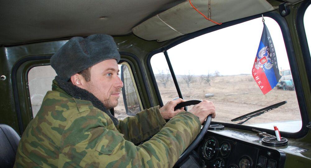 Membro da milícia popular da RPD conduz um veículo militar para o local de exercícios, em finais de 2015