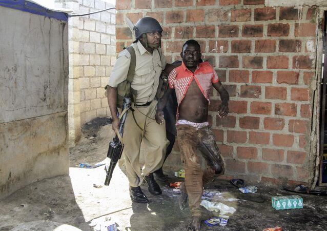 Policial zambiano prende um suposto saqueador no Complexo de Zincalume, onde os moradores atacaram, quebrado e saquearam lojas de estrangeiros em Lusaka