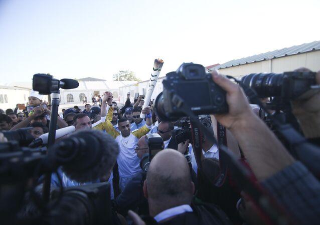 Ibrahim al-Hussein, carrega nesta terça-feira a tocha dos Jogos Olímpicos do Rio-2016 em um campo de migrantes de Atenas