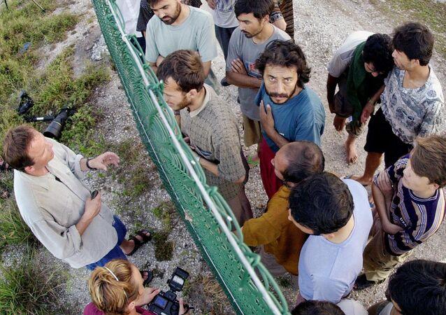 Solicitantes de asilo no centro de detenção australiano na ilha de Nauru conversam com jornalistas estrangeiros.