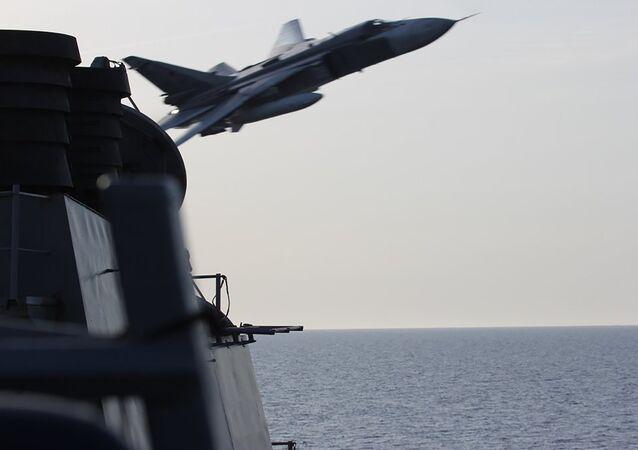 A foto da Marinha dos EUA mostra o que parece ser um avião militar russo voando muito próximo do destroier americano USS Donald Cook.