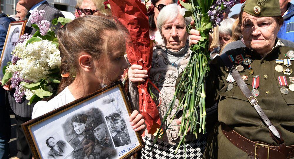 Uma menina e mulheres idosas participam da passeata do Regimento Imortal em 9 de maio de 2016 em Moscou