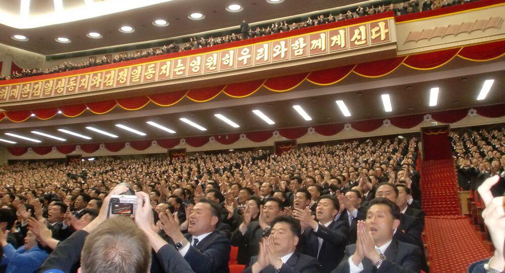 Pessoas presentes na sala do Palácio da Cultura Popular, em Pyongyang, saúdam o líder da Coreia do Norte, Kim Jong-un, na VII Reunião do Partido dos Trabalhadores deste país
