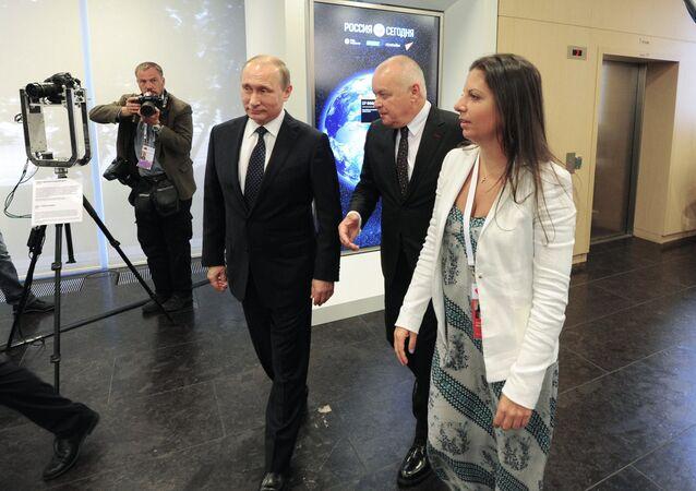 O presidente da Rússia, Vladimir Putin (centro) passeia pela sede da agência internacional de notícias Rossiya Segodnya junto com o diretor-general da mesma, Dmitry Kiselev (segundo da direita) e a editora-chefe da agência e do canal televisivo RT, Margarita Simonyan (direita), em 7 de junho de 2016
