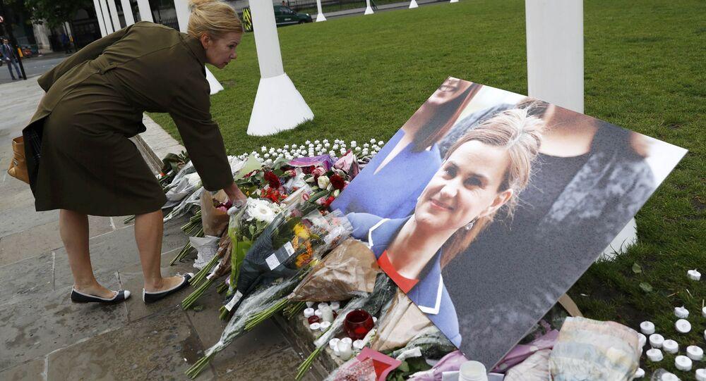 Uma mulher deixa flores ao lado da fotografia de assassinado membro do parlamento laborista Joanne Cox em Parliament Square, Londres, Grã-Bretanha 17 de junho de 2016