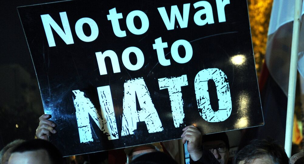 Manifestantes com cartazes dizendo não à guerra, não à OTAN