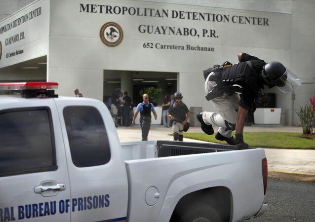 Um policial do batalhão de choque norte-americano salta de carro na frente do centro de detenção de Guaynabo de Porto Rico para acompanhar protesto contra a prisão de Óscar López Rivera