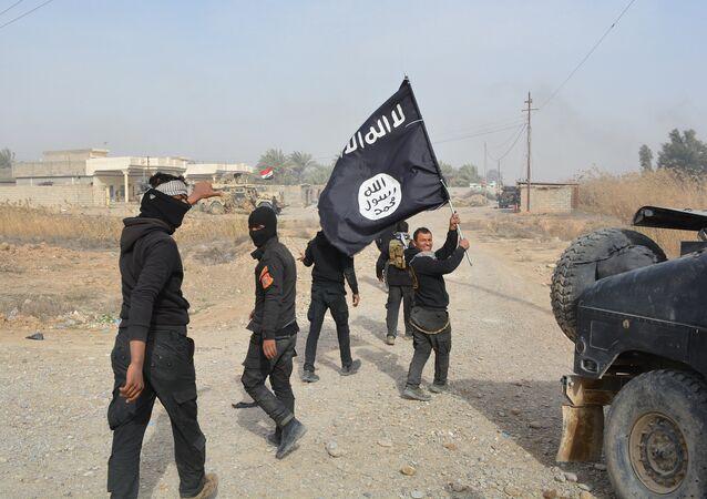 Foto tirada em 26 de janeiro de 2015: soldados do governo iraquiano comemoram retomada do controle sobre a província de Diyala, enquanto um deles exibe uma bandeira apreendida do Daesh