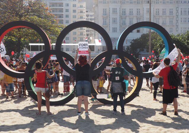 Manifestantes erguem cartazes contra Temer atrás do símbolo dos arcos olímpicos, onde os turistas tiram fotos