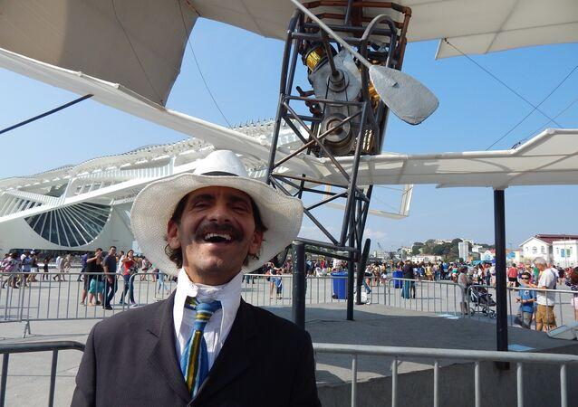 Homem fantasiado de Santos Dumont em frente à réplica do 14-Bis
