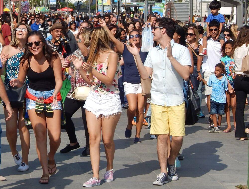 Multidão vibra com músico de rua no Boulevard Olímpico