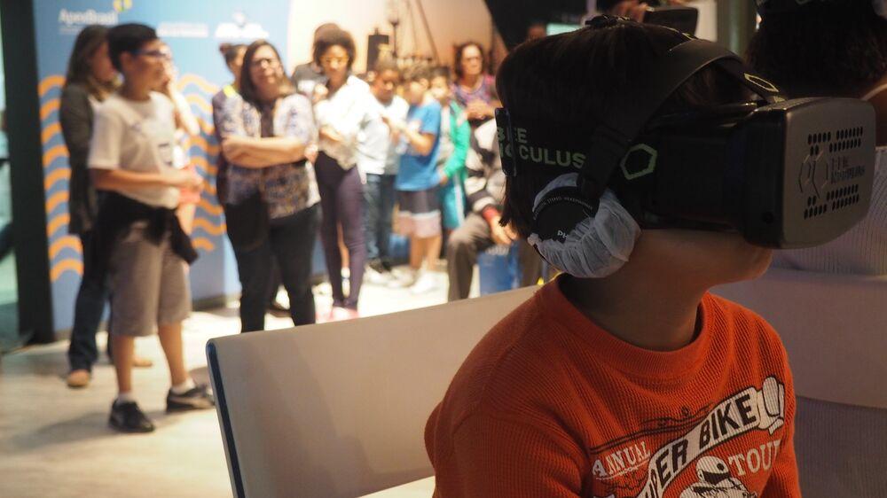 Garoto usa óculos de realidade virtual na Casa Brasil