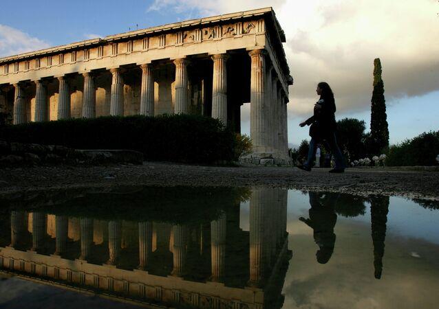 Um turista é refletido em uma poça de chuva enquanto ela passa pelo templo de Ifestos na antiga Ágora de Atenas, Grécia, 2.400 anos de idade. (foto de arquivo)