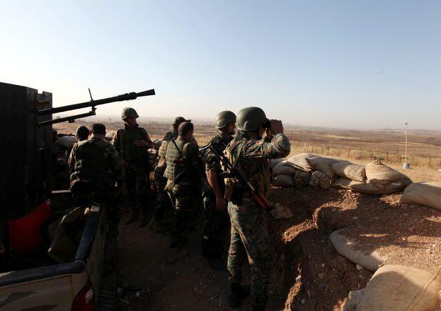 Forças curdas Peshmerga observam aldeia perto da cidade de Mossul no Iraque