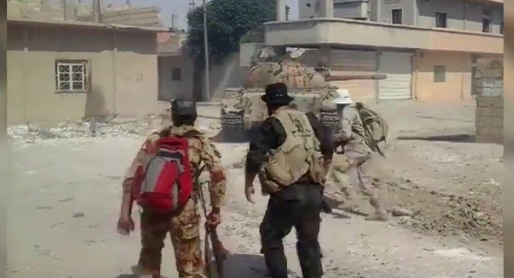 Soldados sírios usam um veículo militar para ir a uma posição segura para combater os terroristas em Al-Hasakah