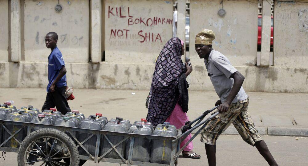 Um jovem passa por uma rua da cidade nigeriana de Kano transportando água, em 8 de abril de 2016; a inscrição na parede diz: Mate Boko Haram e não xiitas