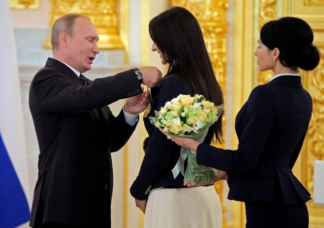 O presidente russo, Vladimir Putin felicita esgrimista Yana Egorian durante a cerimônia para medalhistas olímpicos russos no Kremlin em Moscou, 25 de agosto, 2016