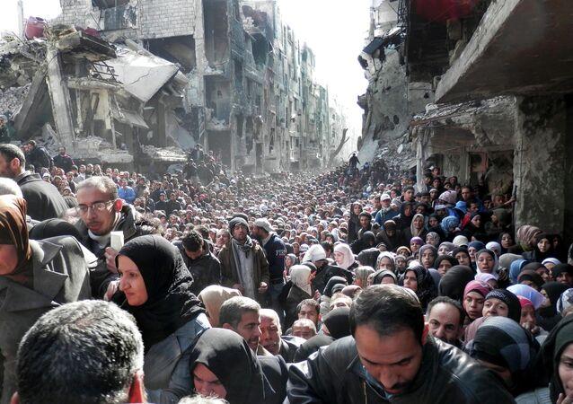 Moradores do campo de refugiados palestinos de Yarmuk, na Síria, fazem fila para receber alimentos