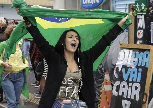 Uma mulher com bandeira do Brasil após a decisão sobre o impeachment de Dilma Rousseff